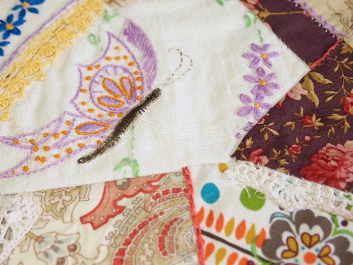 Working with vintage embroidery linens in creating quilt squares.